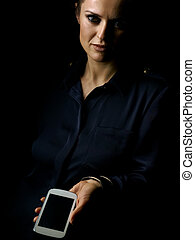 woman in dark dress isolated on black showing smartphone