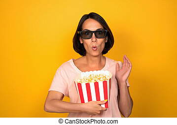 Woman in dark glasses holds box of popcorn. Young brunette with a surprised look raised her hand. Cut out on yellow background in studio. Cinema concept. High quality photo