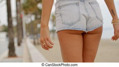Woman in Denim Shorts Walking on Sidewalk - Rear View Close...