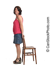 woman in denim skirt playing with a chair on white background,