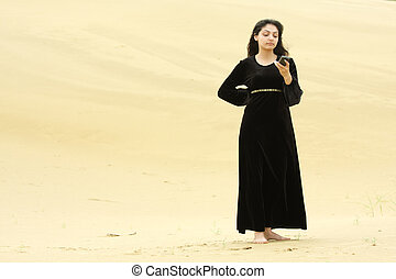 Woman in desert messaging on cellphone