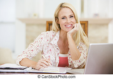 Woman in dining room with laptop frowning