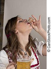 Woman in Dirndl with Beer Mug Taking Shot of Liquor
