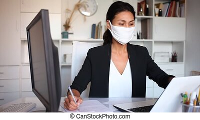Woman in disposable face mask working in business office using laptop