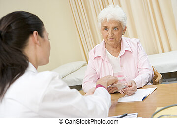 Woman in doctor\\\'s office frowning