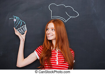 Woman in drawn chef hat holding drawing cupcake over...