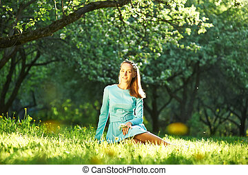 Woman in dress among apple blossoms