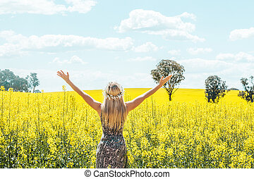 Woman in dress arms in the air standing in front of olden canola fields