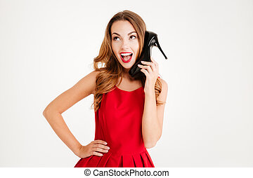 Woman in dress holding high heels shoes at her ear