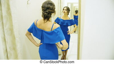 Gorgeous brunette woman in beautiful blue dress standing in fitting room and looking in mirror, customer