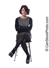 woman in dress sitting on a white background lengs crossed and arms crossed