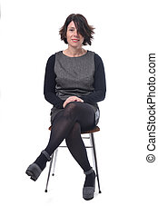 woman in dress sitting on a white background lengs crossed