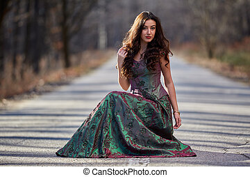 Woman in dress sitting on the road
