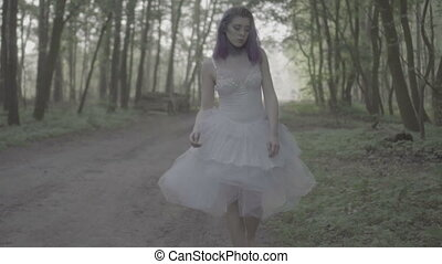 Woman in dress walking in forest.