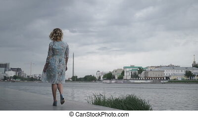 Woman in dress walking on seafront