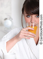 Woman in dressing gown holding glass of orange juice
