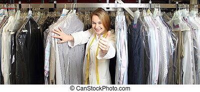 Woman in dry cleaning betwee shirts with thumb up