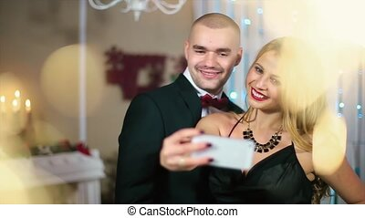 Woman in Evening Black Dress Makes Photo on The phone the man in the black suit in a white room with fireplace and Christmas tree