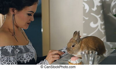 woman in evening dress feeding rabbit fruit
