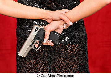 Woman in evening dress with a hidden weapon