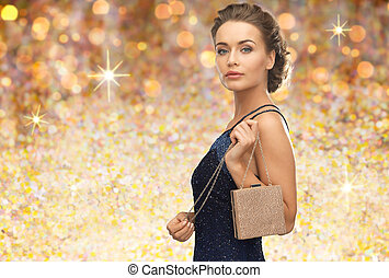 woman in evening dress with bag over golden lights