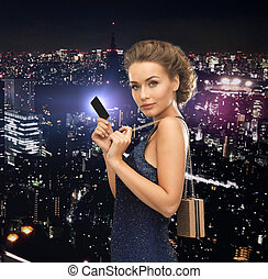 party, celebration, holiday and banking concept - beautiful woman in evening dress with small bag and vip card
