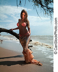 woman in exotic dress standing on the beach - beautiful...