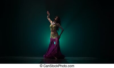 Woman in exotic shining moves her tummy . Smoke background -...