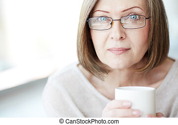 Woman in eyeglasses - Portrait of mature woman with cup ...