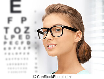 woman in eyeglasses with eye chart - medicine and vision...