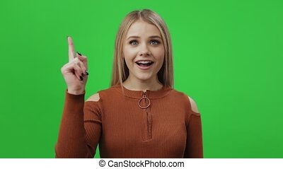 Happy young blonde in eyewear and brown sweater flicking of the fingers and having new idea in her head. Isolated over chroma key background. Understanding and solution concept