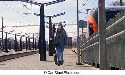 woman in face mask walking along railway platform - health, ...