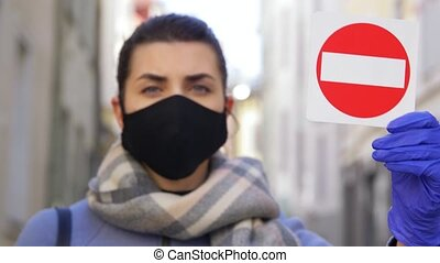 woman in face mask with stop sign in city - health, safety ...