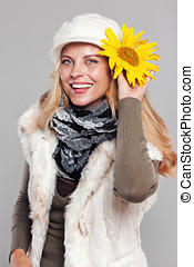 Woman in fall fashion holding a sunflower to her head and...