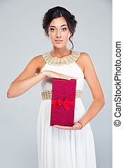 Woman in fashion dress holding gift box