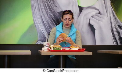 Woman in fast food eating hamburger