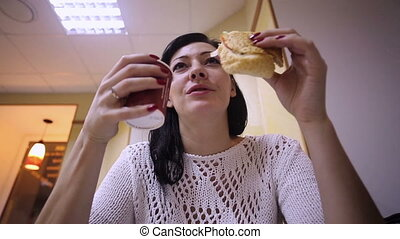 Woman in fastfood eating hamburger
