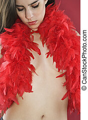 Woman in feather boa. - Partially nude Caucasian woman...