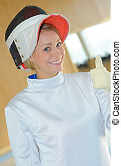 Woman in fencing outfit giving thumbs up