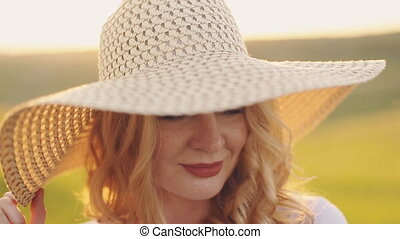 woman in field in straw hat looking at camera