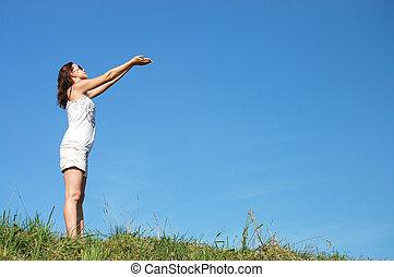 woman in field under blue sky