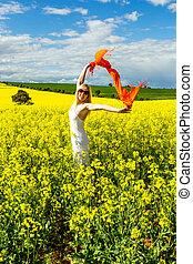Woman in fields of golden canola