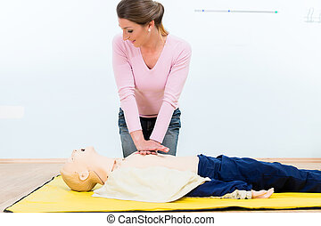 Woman in first aid course practicing heart massage