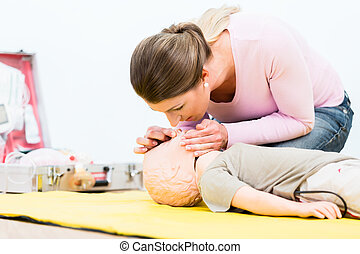Woman in first aid course practicing revival of infant on...