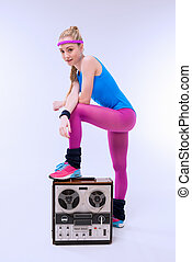 woman in fitness clothing standing on retro record player on white