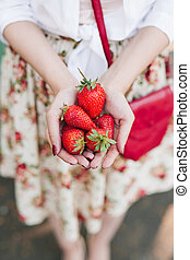 woman in flower dress holding a bunch of strawberries