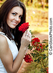 Woman in flower garden smelling red roses