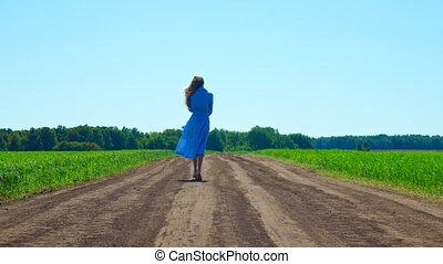 woman in flowing dress removes along way between fields