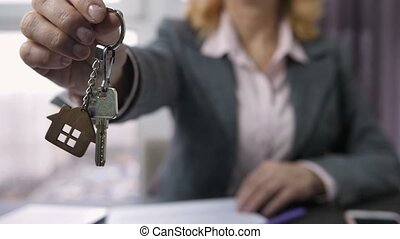 Woman in formal suit showing home keys to camera