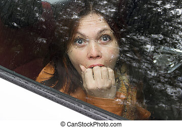 Woman in fright - frightened woman in a car behind the glass...
